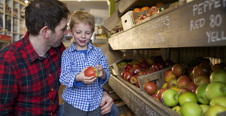 Boy picking out an apple in the supermarket