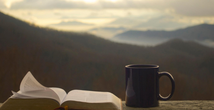 Coffee and the Bible on a rail in front of the mountains