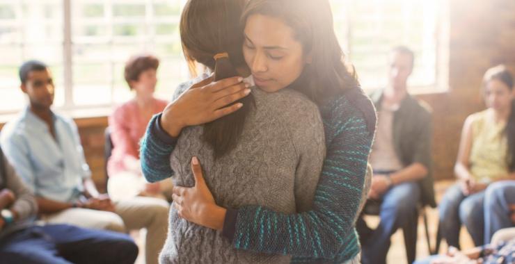Women hugging in prayer circle