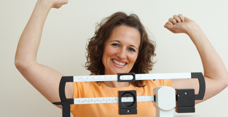 Woman standing in victory pose on scale